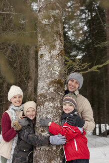 Portrait of happy family hugging tree trunk in snowy woods - CAIF12411