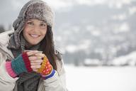 Portrait of happy woman in fur hat drinking coffee in snowy field - CAIF12429