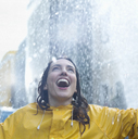 Enthusiastic woman standing in rain - CAIF12441
