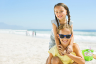 Portrait of smiling girls hugging on beach - CAIF12456