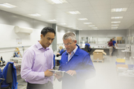 Manager and engineer looking at clipboard in steel factory office - CAIF12510