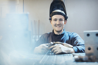 Portrait smiling welder in steel factory - CAIF12555