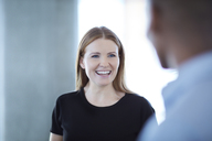 Smiling businesswoman talking to businessman - CAIF12630