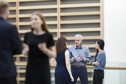 Business people talking in lobby - CAIF12639