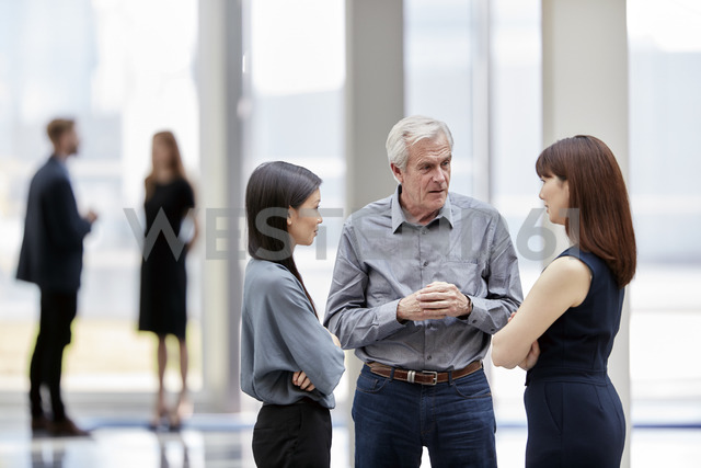 Business people talking in lobby - CAIF12642