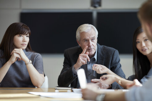 Senior businessman gesturing and talking in meeting - CAIF12645