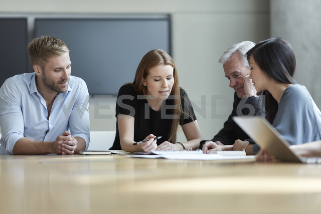 Business people reviewing paperwork in meeting - CAIF12651