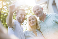 Smiling senior couple and adult son taking selfie outdoors - CAIF12678