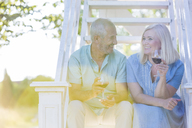 Senior couple drinking wine on summer stairs - CAIF12690