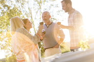 Senior couple and adult children drinking wine on sunny patio - CAIF12696