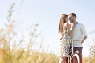 Affectionate young couple with bike hugging in sunny rural field - CAIF12702