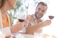 Smiling young couple drinking red wine outdoors - CAIF12708