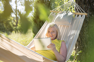 Senior woman using digital tablet and relaxing in summer hammock - CAIF12714