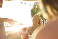 Senior man pouring wine for wife on sunny patio - CAIF12723