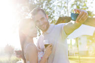 Young couple with wine taking selfie in sunny backyard - CAIF12726