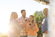 Family talking and drinking wine on sunny patio - CAIF12729
