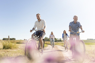 Family riding bicycles on sunny rural dirt road - CAIF12732