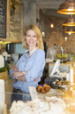 Portrait smiling cafe owner with arms crossed behind the counter - CAIF12759