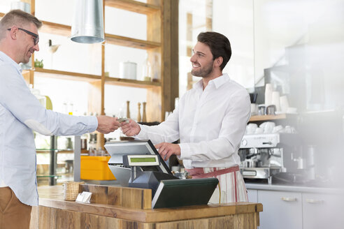 Customer paying worker at cafe cash register - CAIF12771
