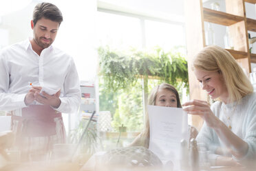 Waiter taking order from mother and daughter in cafe - CAIF12777