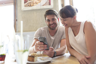 Couple texting with cell phone at cafe table - CAIF12780