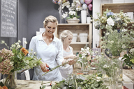 Smiling florists arranging bouquets in flower shop - CAIF12786