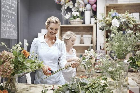 Smiling florists arranging bouquets in flower shop - CAIF12786