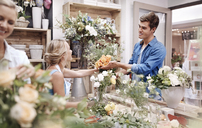 Florist giving man bouquet at flower shop - CAIF12792