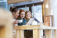 Smiling women drinking tea and sharing digital tablet at cafe counter - CAIF12798