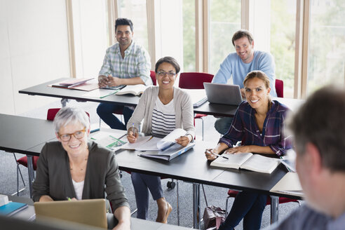 Smiling students watching teacher in adult education classroom - CAIF12852