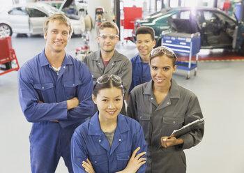 Portrait confident mechanics in auto repair shop - CAIF12888