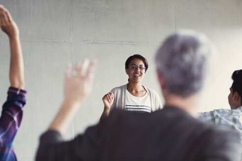 Teacher calling on students with hands raised in adult education classroom - CAIF12891