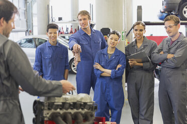 Mechanic and students discussing car engine in auto repair shop - CAIF12894