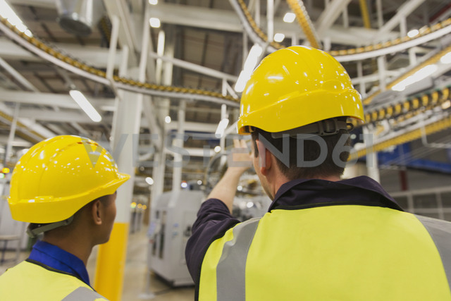 Workers discussing printing press conveyor belts overhead - CAIF12954
