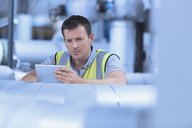 Worker using digital tablet in factory - CAIF12957