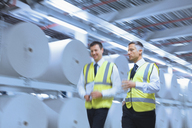 Businessmen in reflective clothing walking along large paper spools in printing plant - CAIF12969