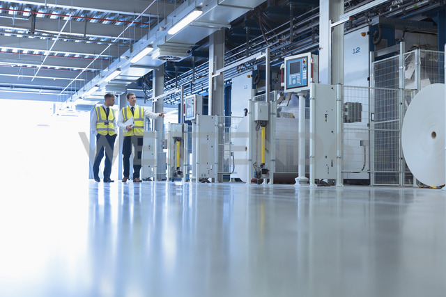 Workers walking along machinery in factory - CAIF12990