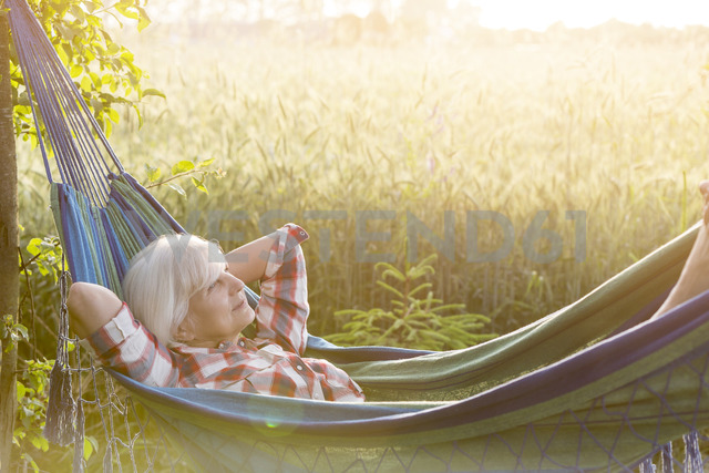 Serene senior woman laying in hammock next to rural wheat field - CAIF13026