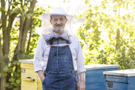 Portrait confident beekeeper in protective hat next to beehives - CAIF13044