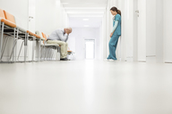 Stressed doctor and nurse in hospital corridor - CAIF13074
