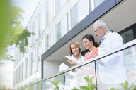 Doctors and nurse reviewing medical record on hospital balcony - CAIF13080