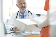 Doctor and nurse reviewing medical record in doctor's office - CAIF13083