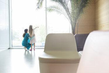 Nurse with pointing girl at hospital lobby window - CAIF13089