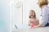 Pediatrician watching girl patient playing with stethoscope in examination room - CAIF13092