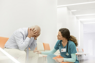 Nurse consoling upset man in clinic corridor - CAIF13104