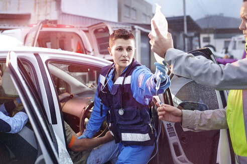 Rescue workers with IV bag tending to car accident victim - CAIF13110
