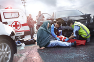 Rescue workers preparing vacuum leg splint on car accident victim in road - CAIF13119