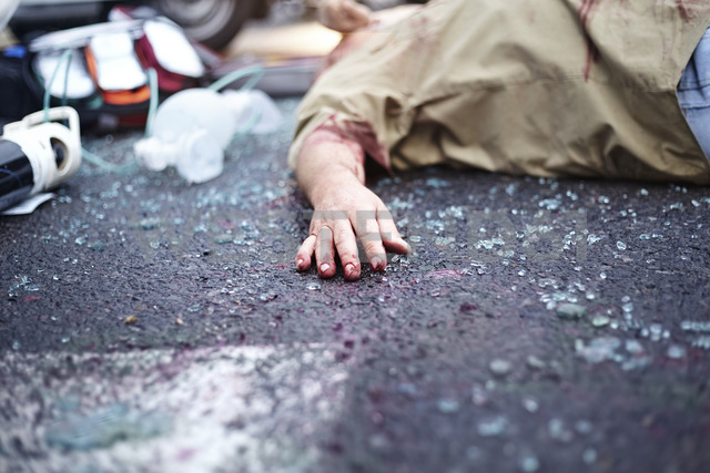 Bloody hand of car accident victim in road among shattered glass - CAIF13125