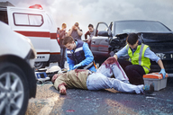 Rescue workers tending to bloody car accident victim in road - CAIF13131