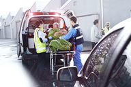 Rescue workers tending to car accident victim on stretcher at back of ambulance - CAIF13140